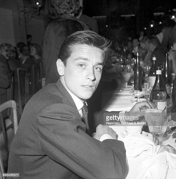 French director and singer Alain Delon sitting at a table of the Vecchia America Corsetti restaurant hosting the Galà del cinema Rome 1959