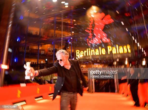 French director Benoit Delepine cheers with hiw trophy The Silver Bear 70th Berlinale on the red carpet after the awarding ceremony of the 70th...