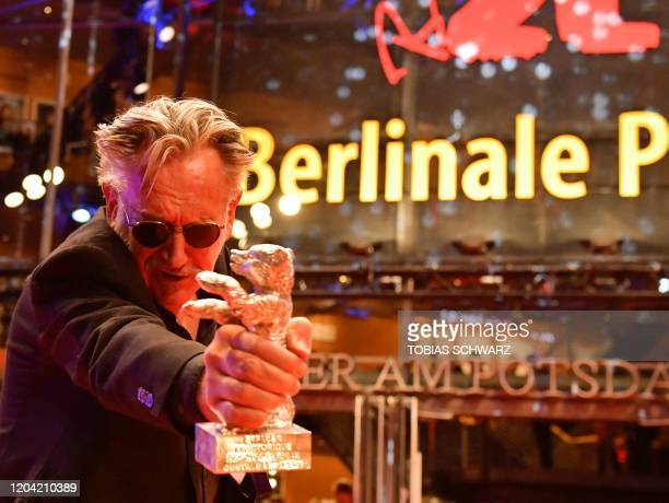 TOPSHOT French director Benoit Delepine cheers with hiw trophy The Silver Bear 70th Berlinale on the red carpet after the awarding ceremony of the...