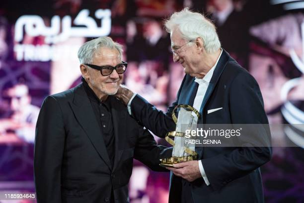French director Bertrand Tavernier is presented with the Etoile d'Or award by US actor Harvey Keitel during the 18th Marrakech International Film...