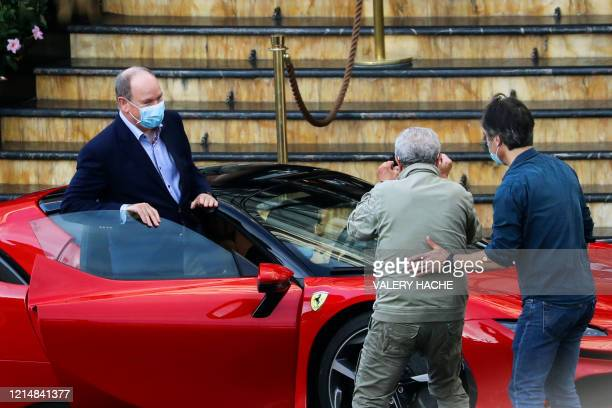 """French director Claude Lelouch films Prince's Albert II of Monaco as he gets in a Ferrari car during the shooting of the short movie """"Le grand..."""