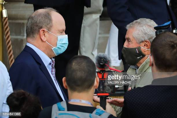 French director Claude Lelouch welcomes Prince's Albert II of Monaco as they both wear a protective facemask on the site of the shooting of the short...