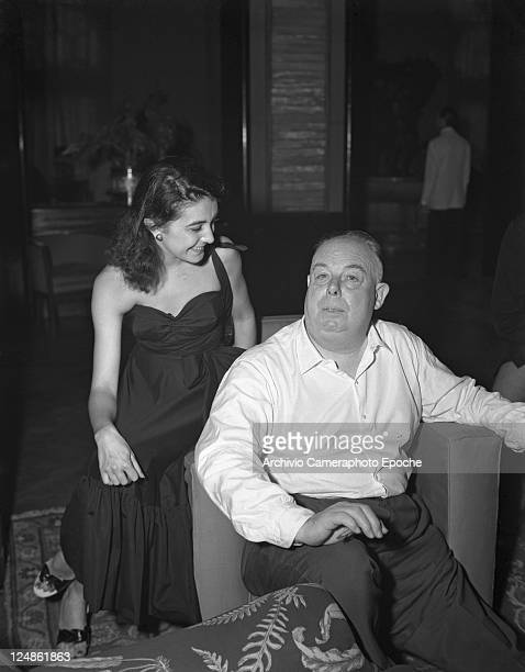 French director Jean Renoir portrayed while sitting on an armchair next to Gianna Sanghe wearing an evening dress Venice Movie festival 1951