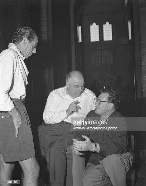 French director Jean Renoirportrayed while talking to the producer Kunnet Mac Edowney a man standing next tho them Venice Movie festival 1951