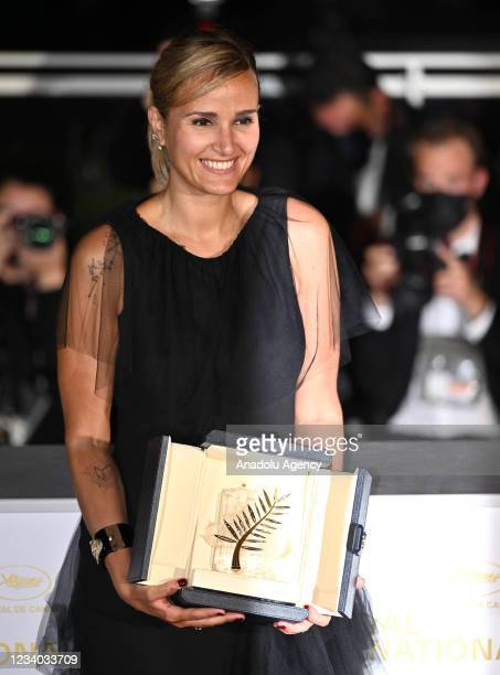 """French director Julia Ducournau poses with her trophy after she won the Palme d'Or for the film """"Titane"""" during the closing ceremony at the 74th..."""