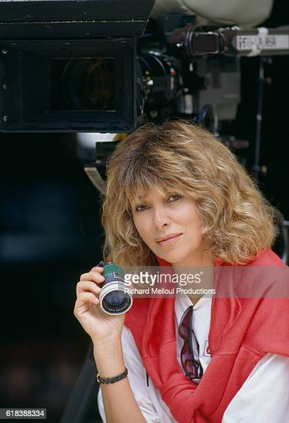French director Mireille Darc holding a loupe on the set of the 1989 film La Barbare In English the title is The Savage The film starred actor Murray...