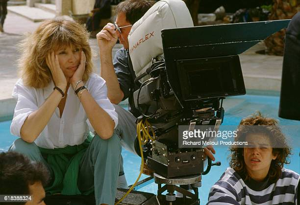 French director Mireille Darc sitting with a film crew during filming of the 1989 film La Barbare In English the title is The Savage The film starred...