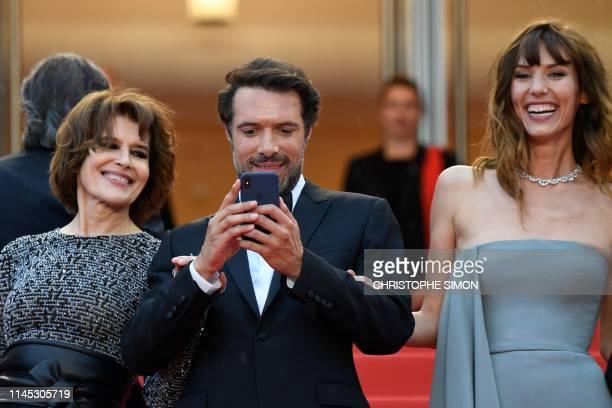 French director Nicolas Bedos takes photos as he arrives with French actress Fanny Ardant and French actress Doria Tillier for the screening of the...