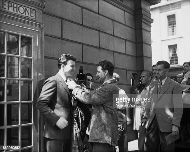 French director René Clément adjusts the tie of his leading man Gérard Philipe during the shooting of the Transcontinental Films production 'Monsieur...