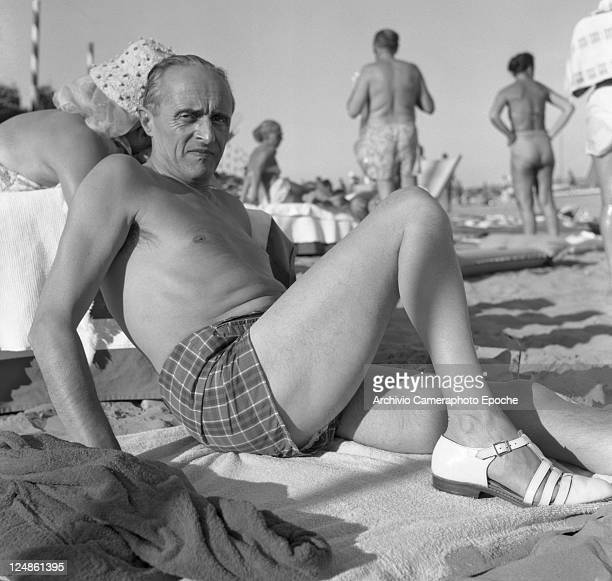 French director Rene Clair wearing a swimming suit and sandals portrayed while lying on the sand Venice Lido beach 1958