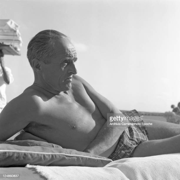 French director Rene Clair wearing a swimming suit portrayed while lying on a sunbed leaning on a pillow Venice Lido beach 1957