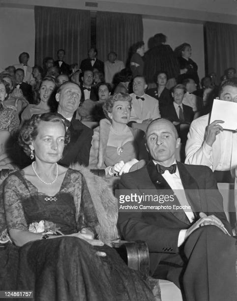 French director Rene Clair wearing a tuxedo and a bow tie portrayed while sitting among the audience french actress Claudette Colbert sitting behind...