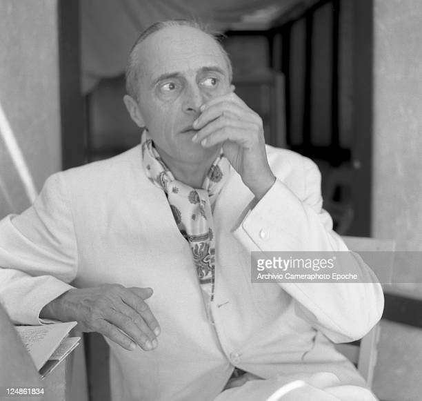 French director Rene Clair wearing a white suit and a foulard portrayed in a closeup while leaning on a table Venice 1958