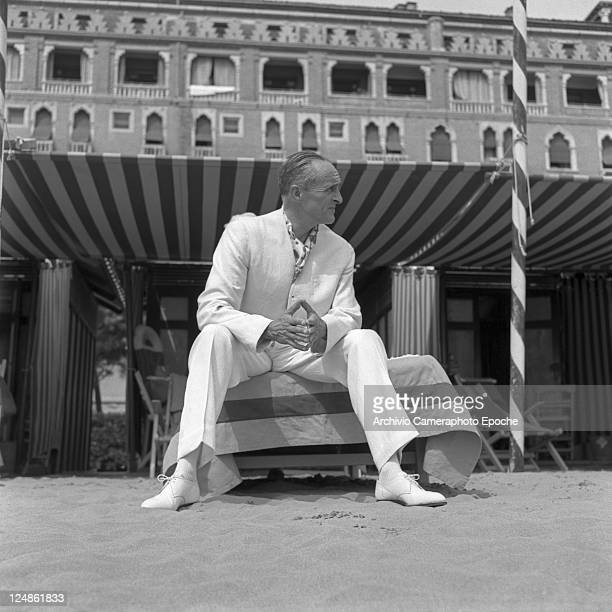 French director Rene Clair wearing a white suit and a foulard portrayed while sitting on a sunbed on the beach the Excelsior hotel in the background...