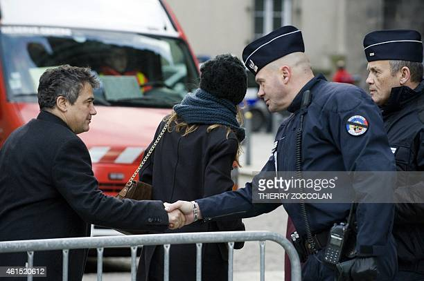 French doctor and contributor to French satirical magazine Charlie Hebdo Patrick Pelloux shakes hand to a policeman with a black band across his...