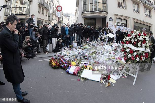 French doctor and contributor to French satirical magazine Charlie Hebdo Patrick Pelloux looks at flowers placed near the offices of French satirical...