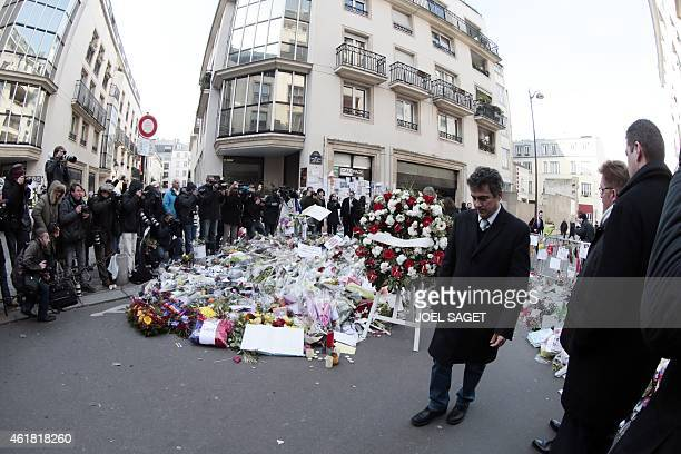 French doctor and contributor to French satirical magazine Charlie Hebdo Patrick Pelloux stands next to flowers placed near the offices of French...