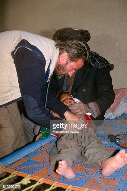 French doctor and politician Bernard Kouchner the cofounder of 'Medecins Sans Frontieres' and Médecins du Monde examines a boy