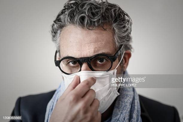 French doctor Michael Bohbot adjusts a protective mask on his face as he poses on March 25 2020 in his cabinet in OrmessonsurMarne a Paris suburb on...