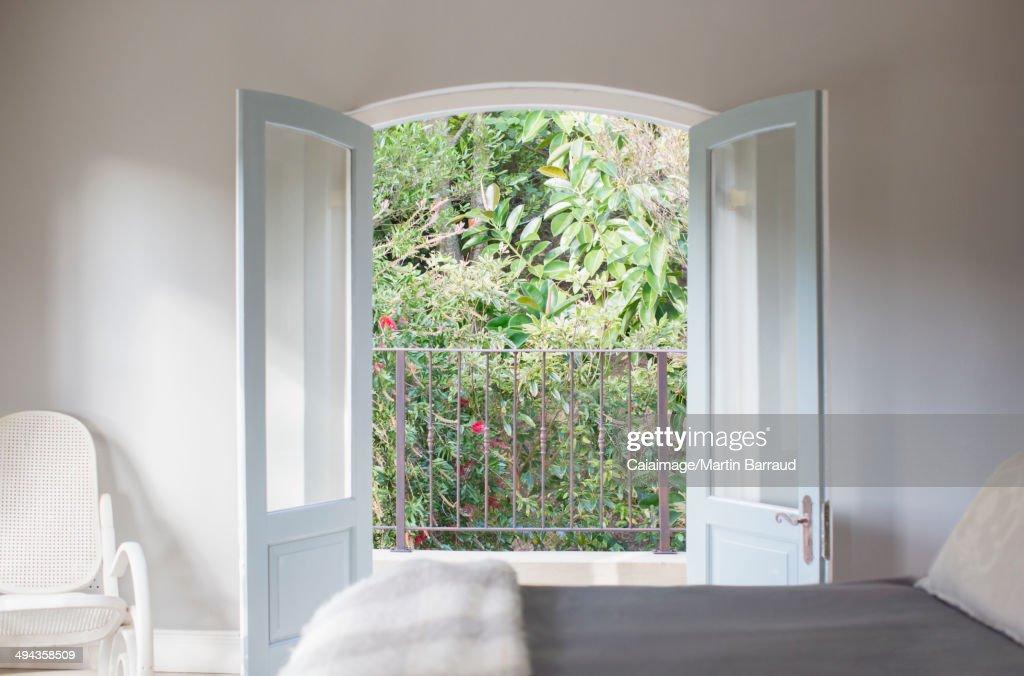 French doors open to balcony in luxury bedroom : Stock-Foto