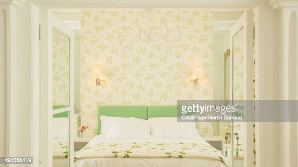French doors open to luxury bedroom with wallpaper