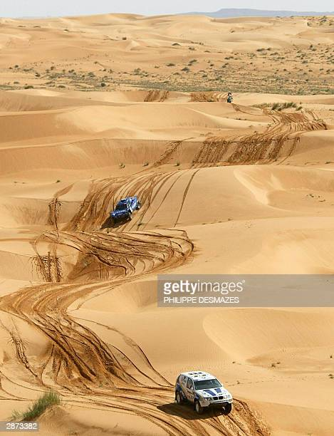 French driver Luc Alphand steers his BMW X4 followed by compatriot JeanLouis Schlesser during the 15th stage between Tidjika and Nouakchott in...