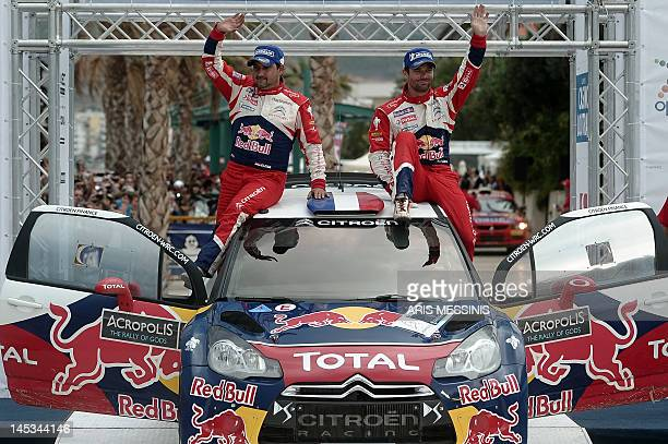 French driver Sebastien Loeb and his codriver Daniel Elena wave to the crowd as they sit on their car after their victory at the WRC Acropolis rally...