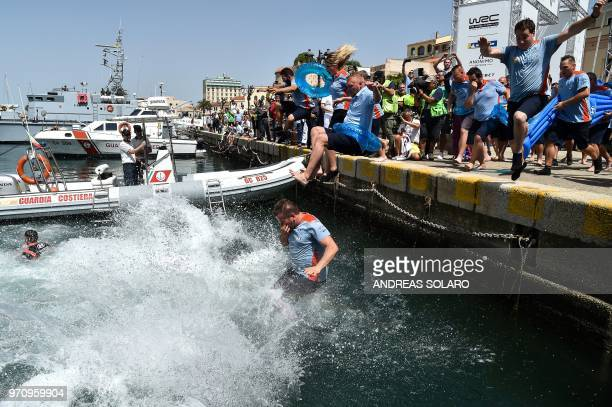 French driver Sebastien Ogier and codriver Julien Ingrassia of Ford Fiesta WRC with their team staff jump in the water as they celebrate after...