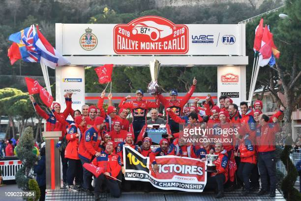 French driver Sebastien Ogier and his codriver Julien Ingrassia hold the trophy as they celebrate with their team after winning the 87th MonteCarlo...