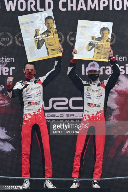 French driver Sebastien Ogier and his co-driver Julien Ingrassia celebrate on the podium after winning the FIA World Rally Championship at the...