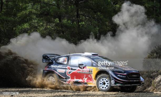 TOPSHOT French driver Sebastien Ogier steers his Ford Fiesta WRC assisted by codriver Julien Ingrassia during the second day of the 2018 FIA World...