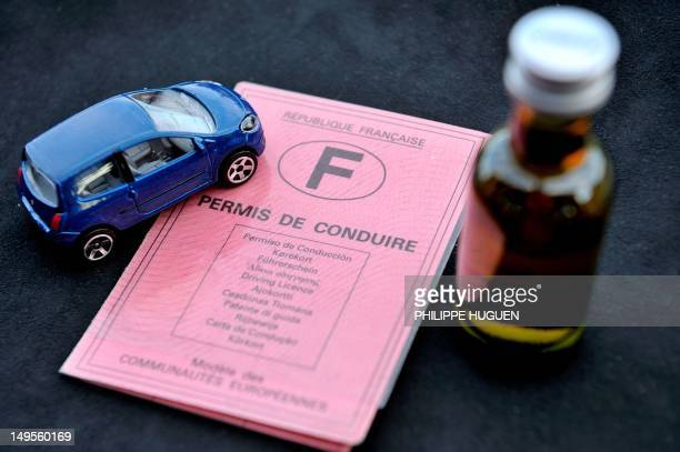 A French driving licence is displayed next to a small bottle of alcohol and a miniature car on July 30 2012 in the French northern city of Lille AFP...