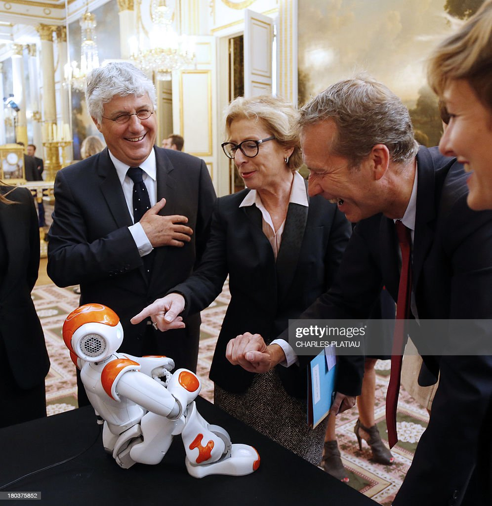 French Ecology and Energy Minister Philippe Martin (L), Minister for External Trade Nicole Bricq (2ndL) and Junior Minister for Food Industry Guillaume Garot (2ndR) look at an humanoid robot 'Nao' from Aldebaran Robotics company as they visit an exhibition on French industrial design and technology at the Elysee Palace on September 12, 2013 in Paris.