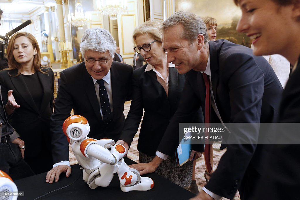 French Ecology and Energy Minister Philippe Martin (2ndL), Minister for External Trade Nicole Bricq (2ndL) and Junior Minister for Food Industry Guillaume Garot (2ndR) look at an humanoid robot 'Nao' from Aldebaran Robotics company as they visit an exhibition on French industrial design and technology at the Elysee Palace on September 12, 2013 in Paris.