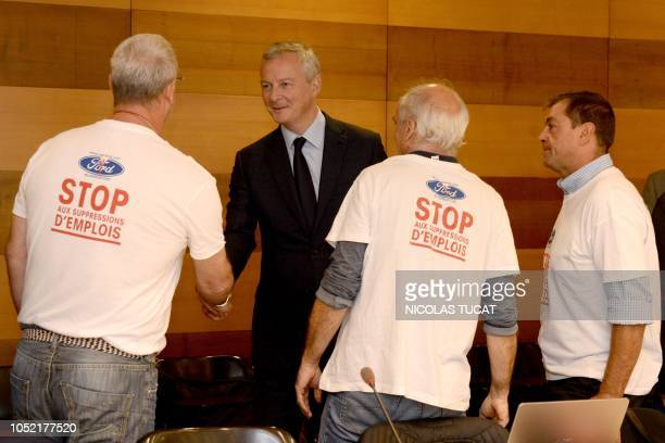 French Economy and Finance Minister Bruno Le Maire shakes hands with Ford Blanquefort unionists as he arrives for a meeting on October 15 2018 in...