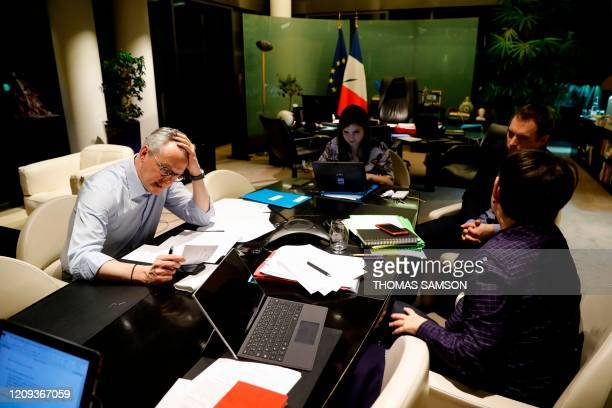 TOPSHOT French Economy and Finance Minister Bruno Le Maire speaks on the phone with his German counterpart as his advisor Juliette Oury his cabinet...