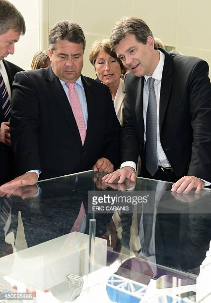 French Economy and Industry Minister Arnaud Montebourg and German Minister for Economic Affairs and Energy Sigmar Gabriel look at a model of...