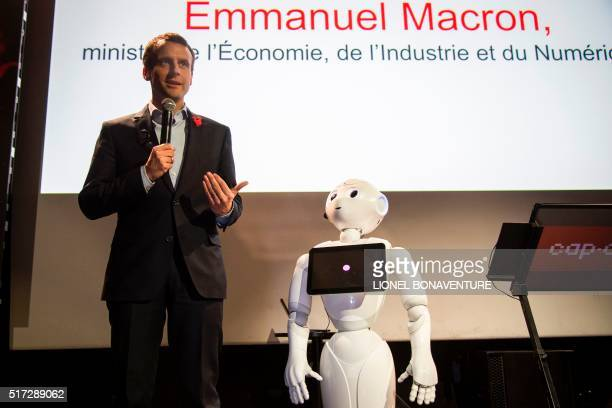 French Economy and Industry Minister Emmanuel Macron speaks next to Pepper an Aldebaran Robotics' robot during the 10th anniversary of Cap Digital...