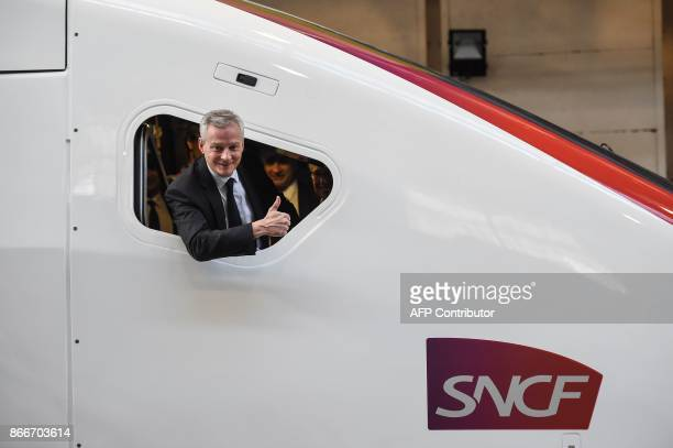French Economy Minister Bruno Le Maire gestures from a train window as he visits the site of French train maker Alstom in Belfort on October 26 2017...