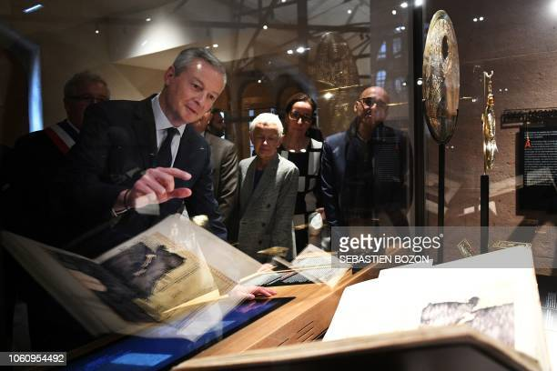 French Economy Minister Bruno Le Maire looks at an old book as part of the inauguration of the new Humanist Library in Selestat eastern France on...
