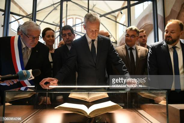 French Economy Minister Bruno Le Maire looks at an old book watched by mayor of Selestat Marcel Bauer , French right-wing Les Republicains party...