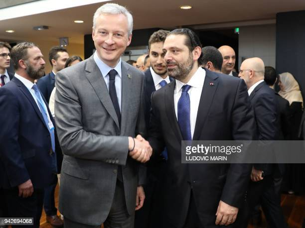 French Economy Minister Bruno Le Maire shakes hands with Lebanese Prime Minister Saad Hariri as they attend the Cedre conference at The Foreign...