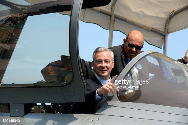French Economy Minister Bruno Le Maire sits in French Dassault Aviation Rafale jetfighter flanked by Dassault Aviation Chief Executive and French...