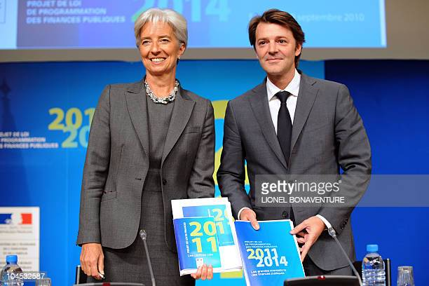 French Economy minister Christine Lagarde and Budget minister Francois Baroin show France's 2011 budget documents during a press conference on...