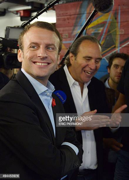 French Economy Minister Emmanuel Macron listens to Founder of French telecom and Internet company Iliad, and president of the private computer...