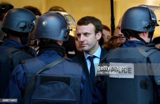 French Economy Minister Emmanuel Macron talks with policemen while visiting Les 4 Temps shopping center in La Defense business district near Paris on...