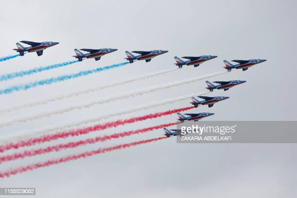 TOPSHOT French elite acrobatic flying team Patrouille de France performs a flying display over Paris during the annual Bastille Day military parade...