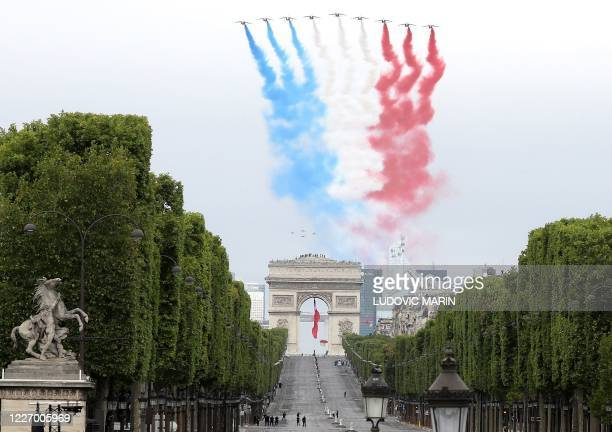 TOPSHOT French elite acrobatic flying team Patrouille de France performs a flying display of the French national flag over the Arc de Triomphe during...