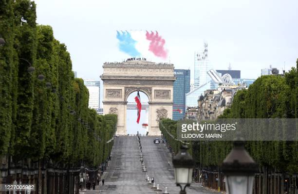 French elite acrobatic flying team Patrouille de France performs a flying display of the French national flag over the Arc de Triomphe during annual...