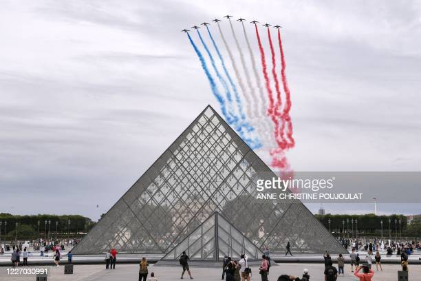 French elite acrobatic flying team Patrouille de France performs a flying display of the French national flag over the Louvre pyramid designed by...